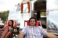 Young couple relaxing outside RV camper near seaside