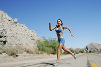 Young woman running on open road outdoors.