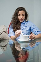 Young woman stirring tea in office