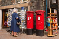 A woman choosing a postcard at The Post Office shop store at Keswick , Cumbria , England , Great Britain , Uk