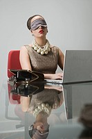 Young woman wearing eye mask, using laptop