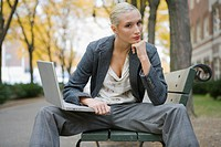 Portrait of young blonde woman holding laptop on bench in neighborhood