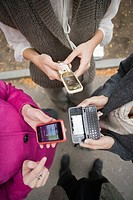 High angle view of young women in park text messaging on cell phones