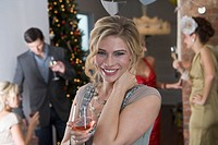 Portrait of smiling blonde woman having a drink at holiday party with friends