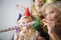 Close_up of young adult friends with party blowers and drinks at Christmas party