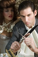 Portrait of sexy couple at dinner party, man holding knife and fork