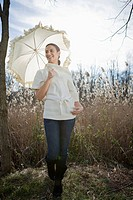 Beautiful young woman enjoying with umbrella in field