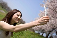 Young woman taking a picture with mobile phone, Kyoto Prefecture, Honshu, Japan