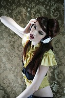 Portrait of glamourous young woman listening to headphones in room with wallpaper