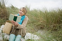 Woman reading a book on a dune