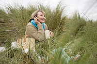 Woman at the coast with mug and cellphone