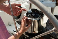 Father and son on board yacht, father pointing to speedometer
