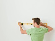 Young man using spirit level on wall (thumbnail)