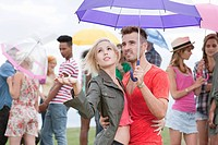 Young couple under umbrella at festival, testing for rain