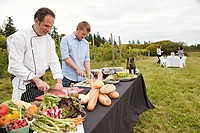 Men preparing food for dinner party in field