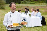 Chef with meal and people at dining table in a field