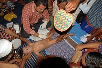 A naked four year old boy Muslim lays on his back undergoing the rite of circumcision family members hold the boy whle the doctor swabs the gental are...