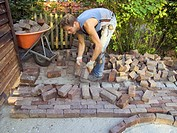cobblestone bricklayer making an ornamental pavement