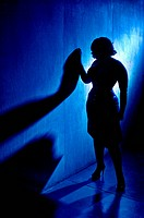 Silhouette of a woman leaning against the wall, with blue light.