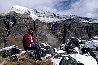 TREKKER sits on the rock below a HIMALAYAN PEAK in the ANNAPURNA SANCTUARY _ NEPAL