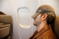airplane passenger trying to sleep during flight