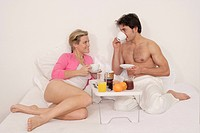 Couple having breakfast on bed