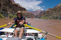 Rafting guide Todd Lovell rows down the COLORADO RIVER near mile 130 _ GRAND CANYON NATIONAL PARK, ARIZONA