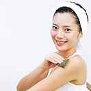 a woman putting green tea pack on her arms