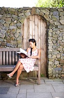 a woman reading a book with sitting on the wooden bench in front of stone wall