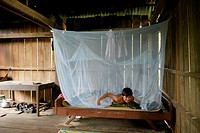 CAMBODIA  Phala Lekha 15 arranging the mosquito net over his bed, Kamphun village, Stung Treng district
