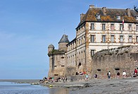Tourists on beach in front of the Mont Saint_Michel abbey, Normandy, France