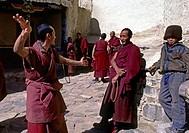 Monks practicing ritualized TIBETAN BUDDHIST debate at TASHILHUNPO MONASTERY _ SHIGATSE, TIBET