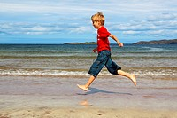 boy running on sandy beach, Sutherland, Scotland