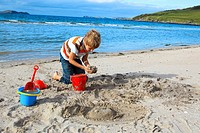 boyl playing on sandy beach, Sutherland, Scotland