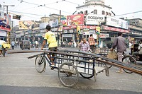 Street scene , cycle rickshaw rider riding heavy load , Calcutta now Kolkata , West Bengal , India
