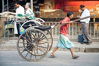 Street scene , hand rickshaw puller pulling empty vehicle , Calcutta now Kolkata , West Bengal , India