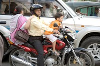 Parent and child sitting on two wheeler bike traffic jammed on street , Dhaka , Bangladesh