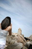 Thailand, Koh Samui Island. Thai woman taking pictures of famous phallus shaped rock