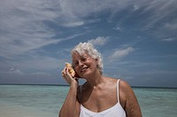 Maldives, Ari Atoll, senior woman listening to a sea shell