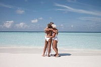 Maldives, Ari Atoll, three people embracing