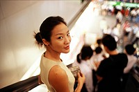 Thailand, Bangkok, asian woman on escalator