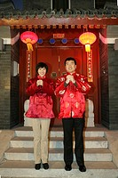Chinese family gesturing welcome at the gate celebrating Chinese New Year