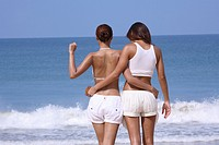 Two women standing on beach, back view