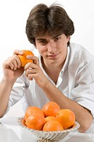 Young man holding holding an orange