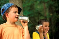 Kids use tin cans to make a telephone.