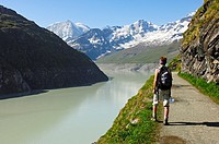 Hiker at the storage lake Lac des Dix with Mt  Mont Blanc de Cheilon in the back, Val d'Herens valley, Valais, Switzerland