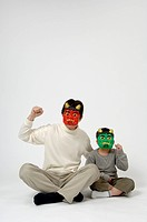 Father and son wearing mask of evil