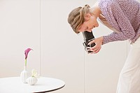 Woman photographing flowers in vases with retro camera (thumbnail)