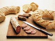 Tuscan and umbrian boar salami with slices cut and white bread ring