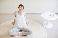 Smiling woman sitting cross_legged on rug